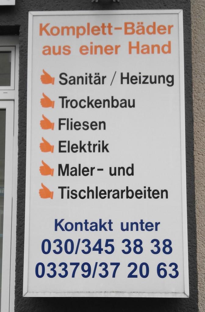 Das Bild zeigt ein Firmenschild auf dem der Schrägstrich einmal mit und einmal ohne Leerschritte verwendet wird.