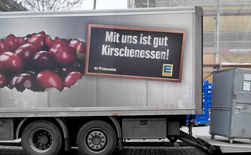 """Das Bild zeigt einen LKW mit dem Werbeaufdruck """"Mit uns ist gut Kirschenessen"""". Kirschen essen müsste in dieser Verwendung getrennt geschrieben werden."""