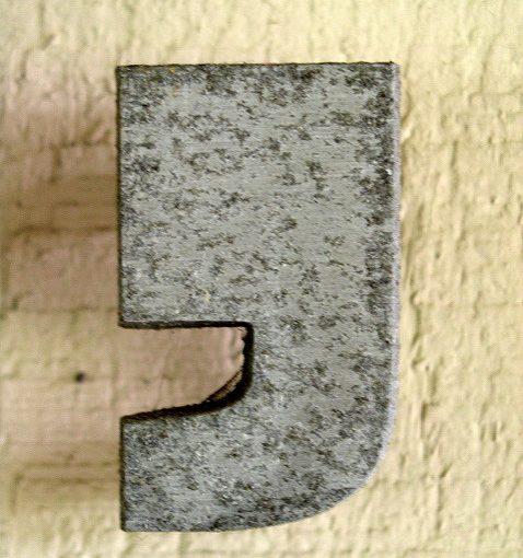 Das Foto zeigt ein Komma aus Metall an einer Wand.