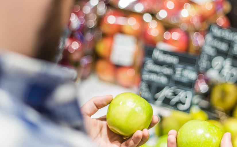 Komma sowohl als auch: Das Bild zeigt einen Mann, der sich zwischen zwei identischen Äpfeln entscheidet.